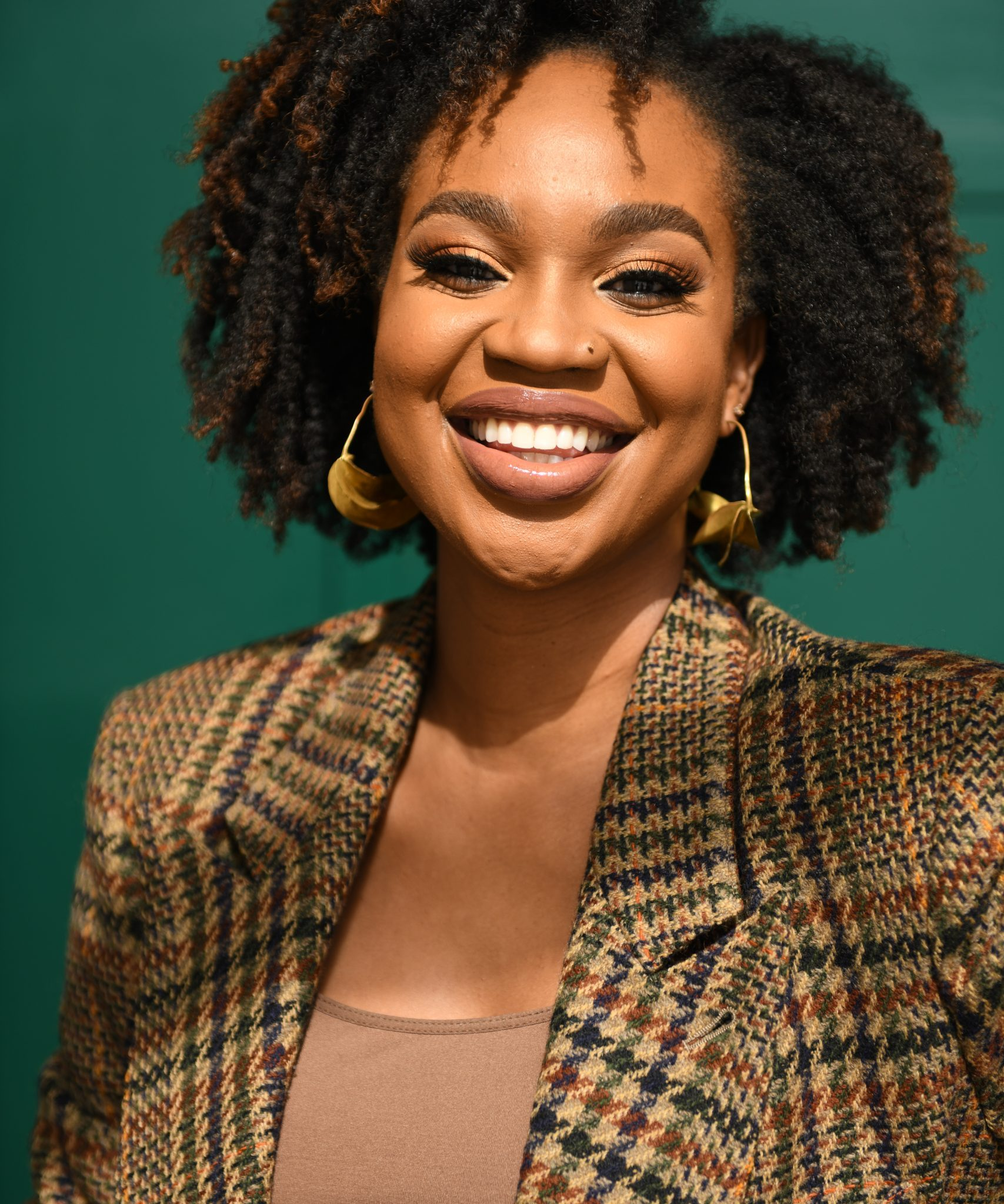 Ijeoma Kola headshot on green background - hairstyles for black women