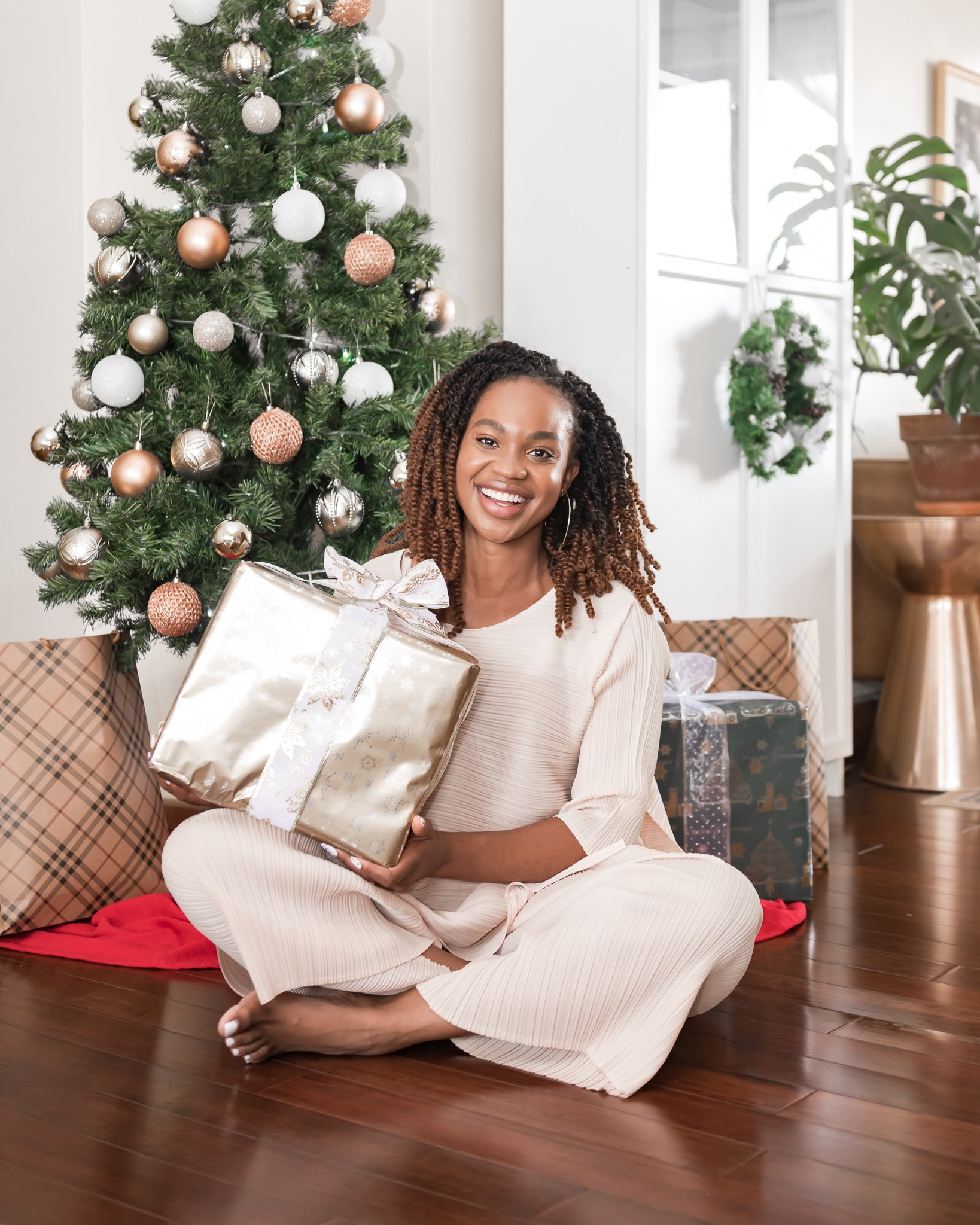 Ijeoma Kola smiling with gold gift box in hands in front of decorated Christmas tree