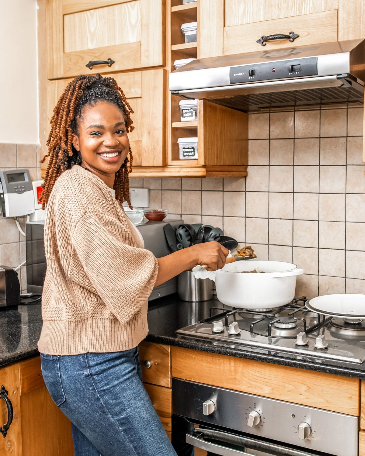 Ijeoma Kola Cooking curry goat in white pot in kitchen