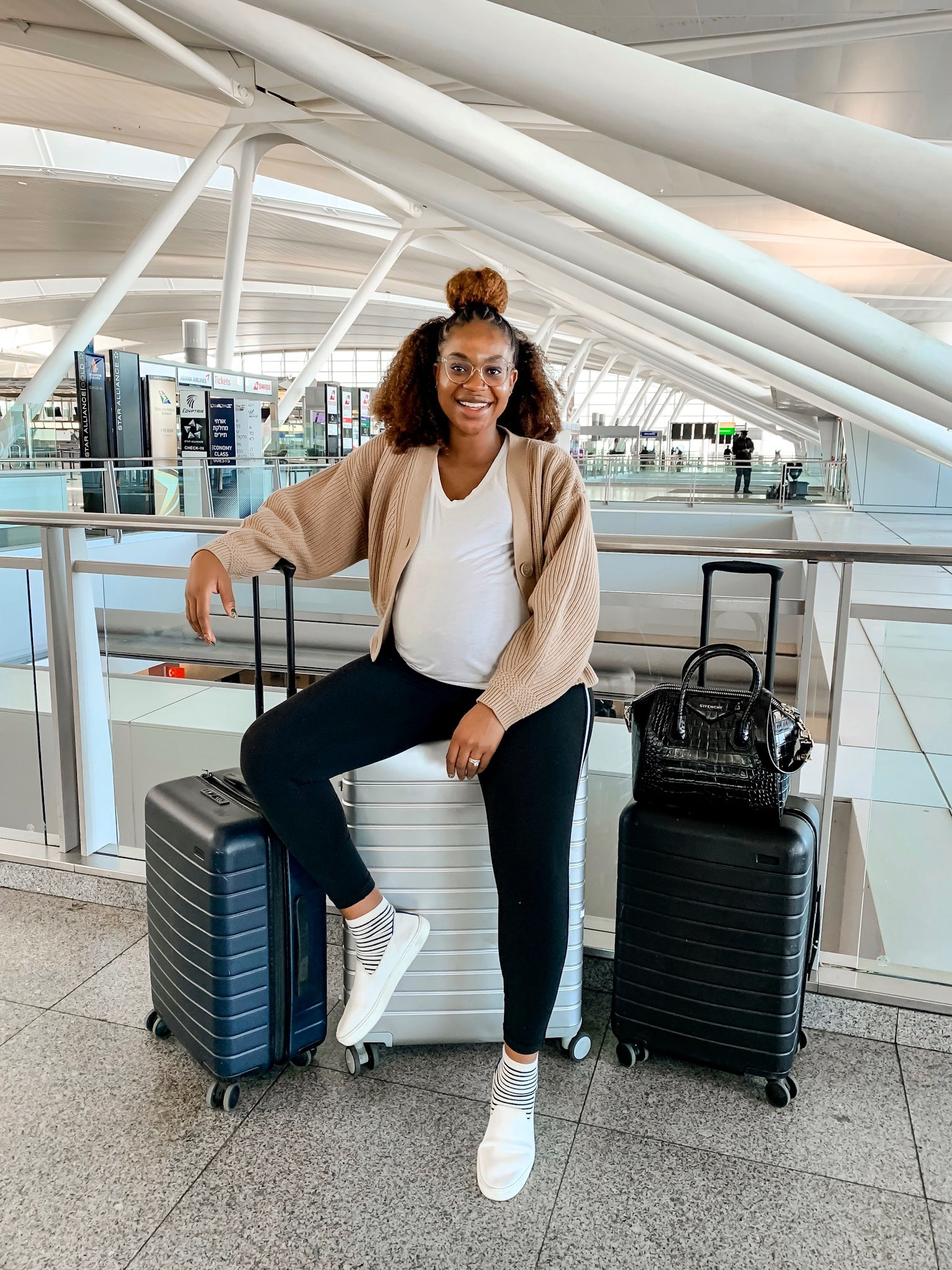 Ijeoma Kola at airport with luggage. Travel safely for the holidays.