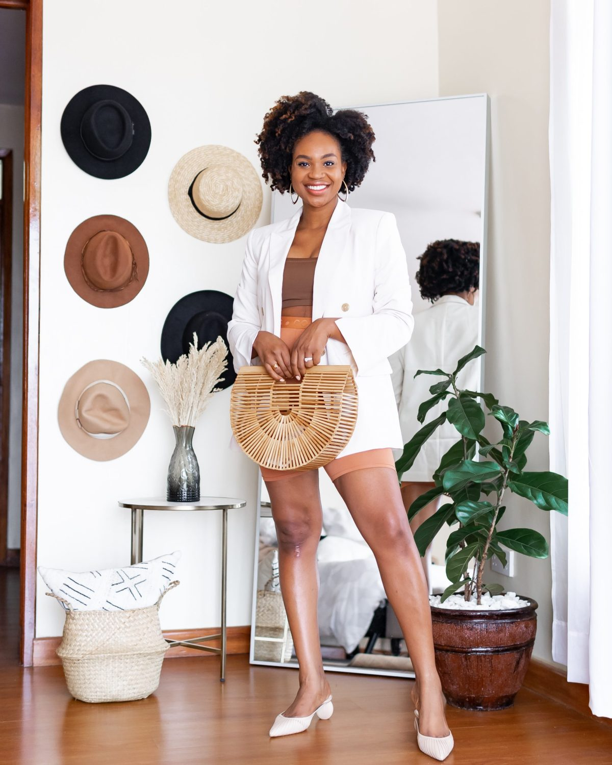 Ijeoma Kola in white blazer and brown biker shorts