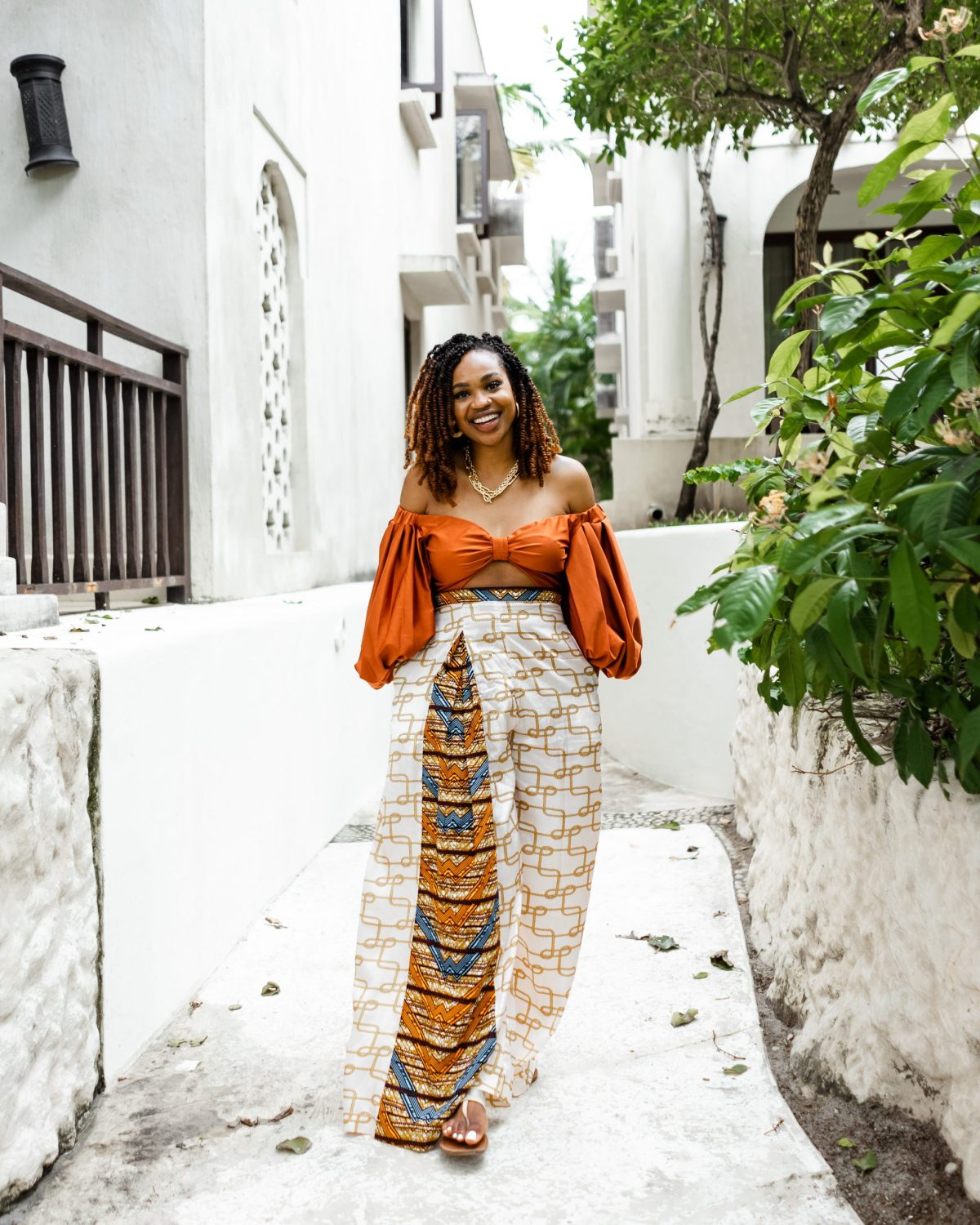 Ijeoma Kola in orange puffy sleeved top and print pants