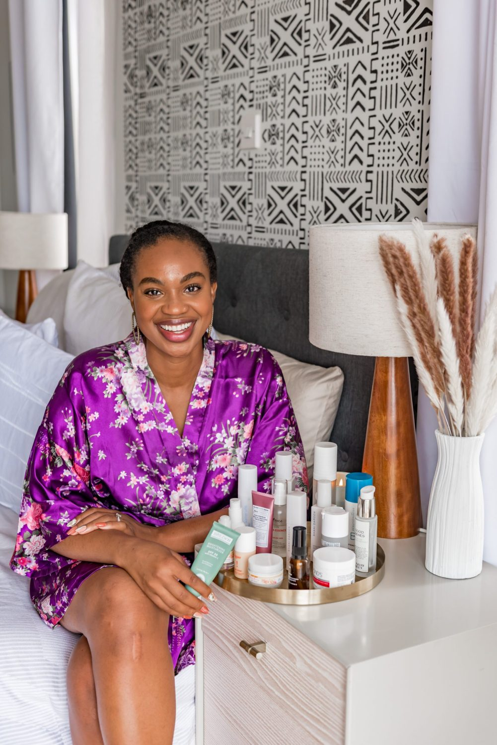 IJeoma.  kola.in purple silk robe sitting on bed with skincare products on tray