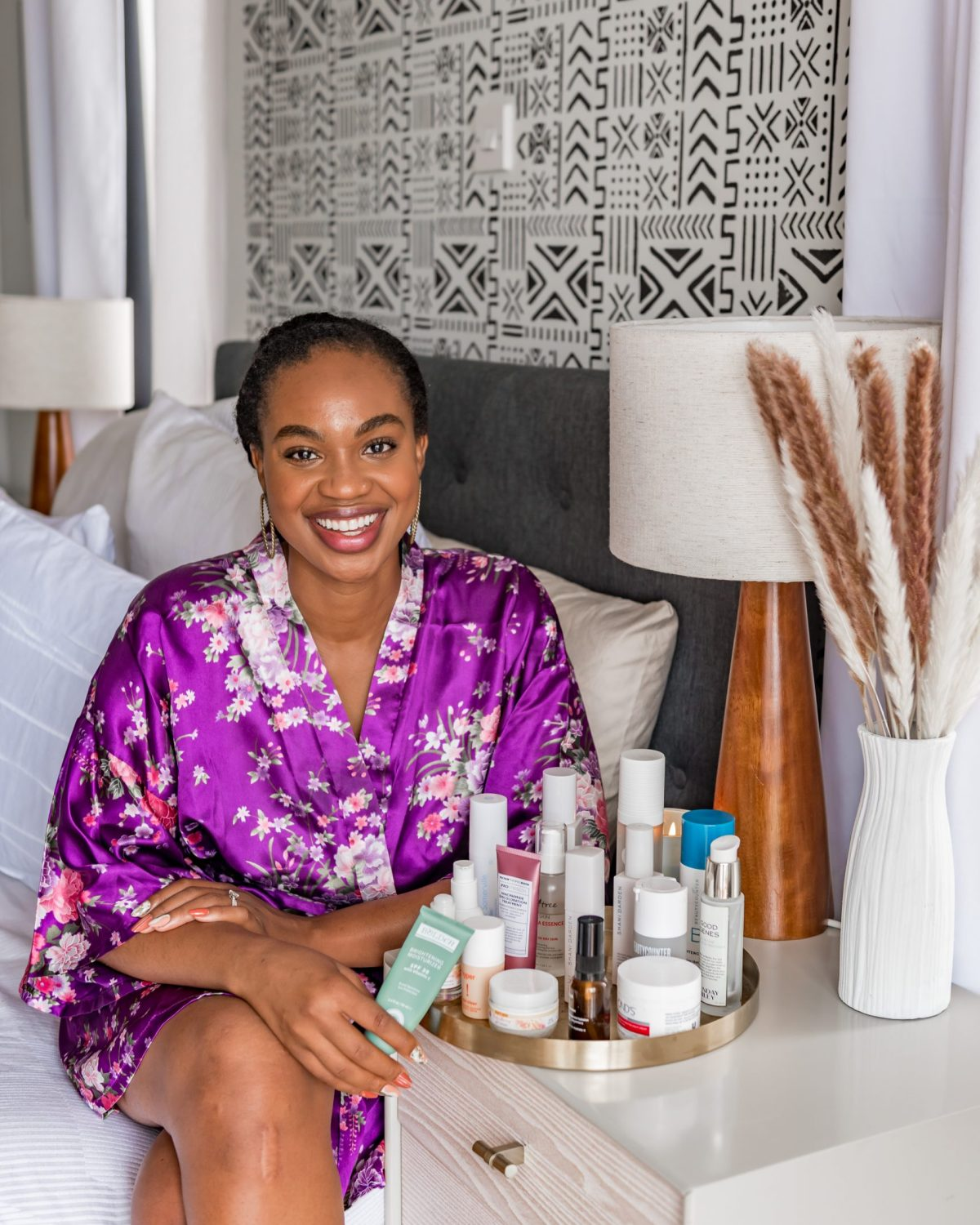 Ijeoma Kola in purple silk robe sitting on bed with skincare products on tray
