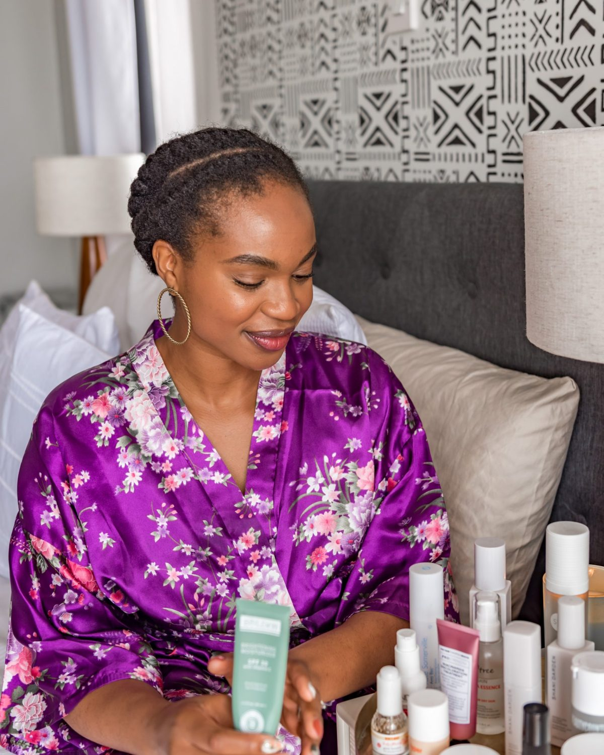 Ijeoma Kola sitting on bed in purple silk robe with skincare product doing Morning Skincare Routine
