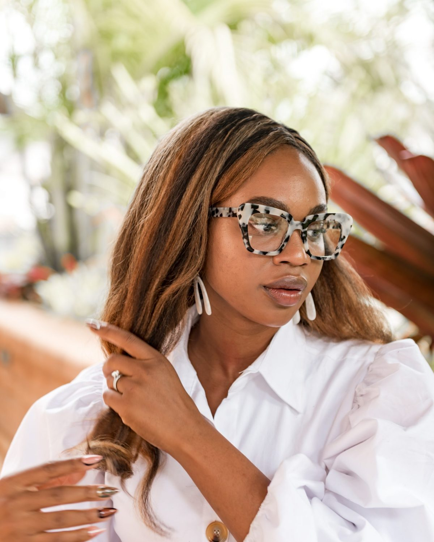 Ijeoma Kola touching hair and wearing animal print glasses - Blog about mental health and social media