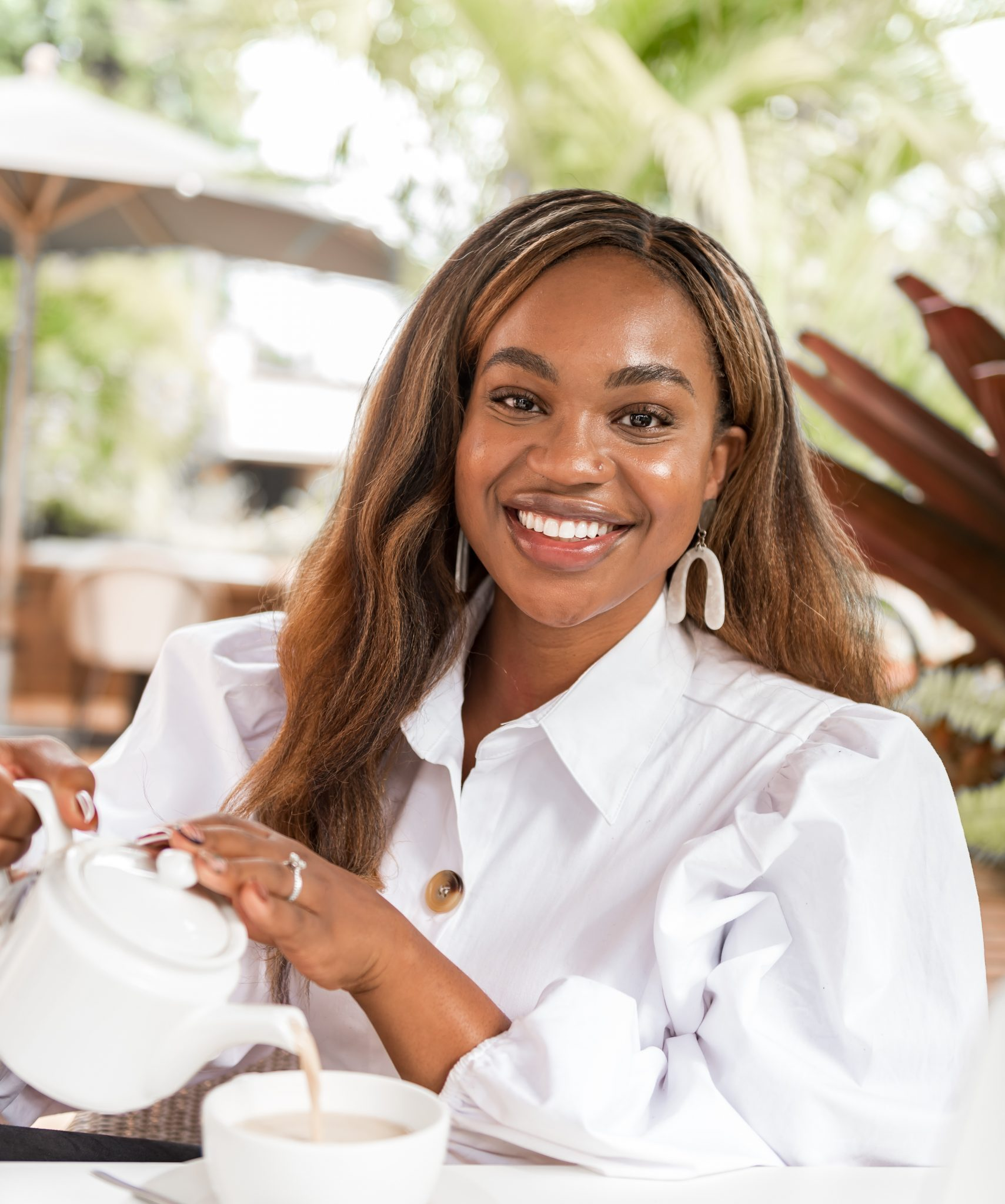 Ijeoma Kola smiling as she pour tea into tea cup at a café
