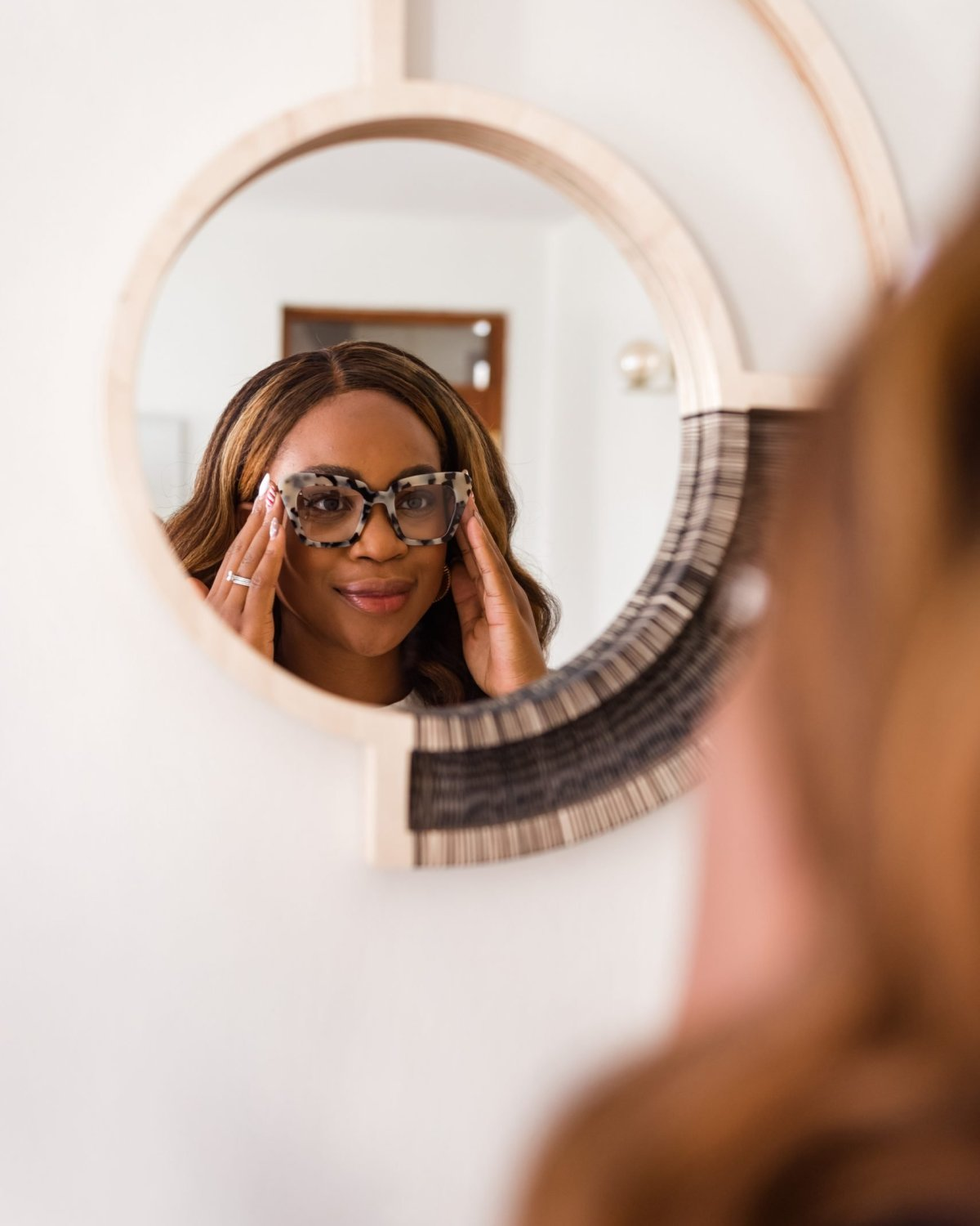 Ijeoma Kola looking in round wall mirror while adjusting eyeglasses