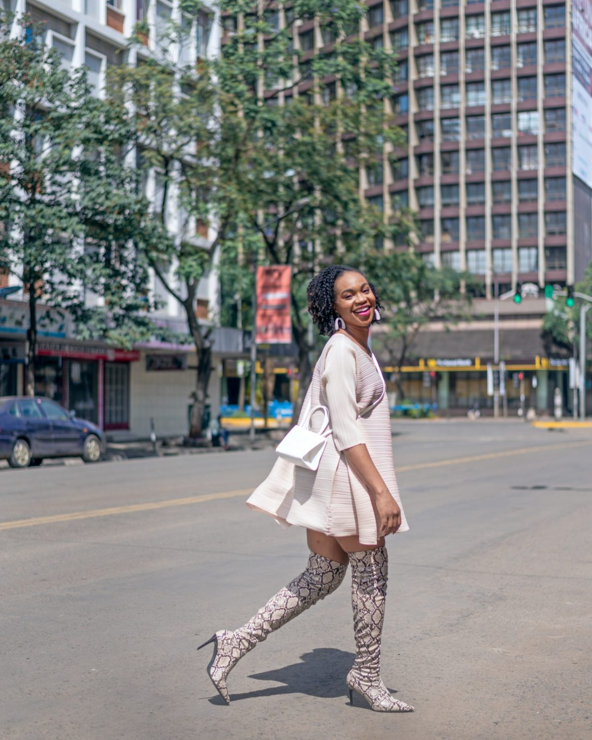 Ijeoma Kola posing in the streets of Nairobi wearing cream mid-sleeve dress, white shoulder sling bag and snake skin thigh high boots - Blog on how to make extra money