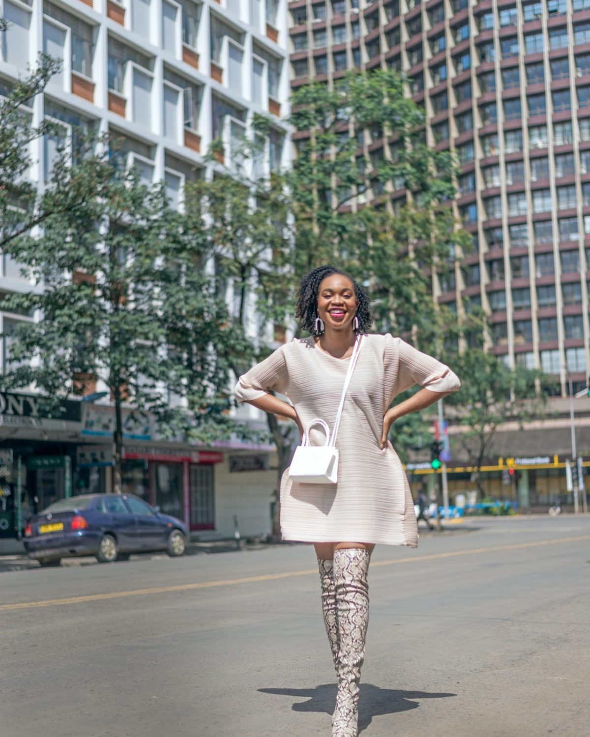 Ijeoma Kola posing with hands on hips in the streets of Nairobi wearing cream mid-sleeve dress, white shoulder sling bag and snake skin thigh high boots - Blog on how to make extra money