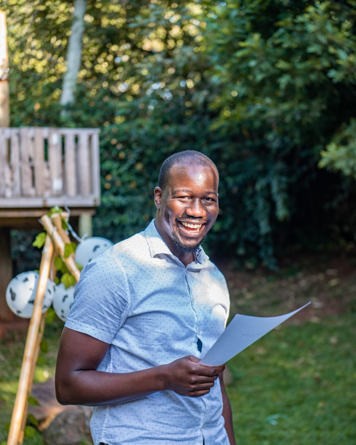 Jonathan Kola smiling outdoors with paper in hand
