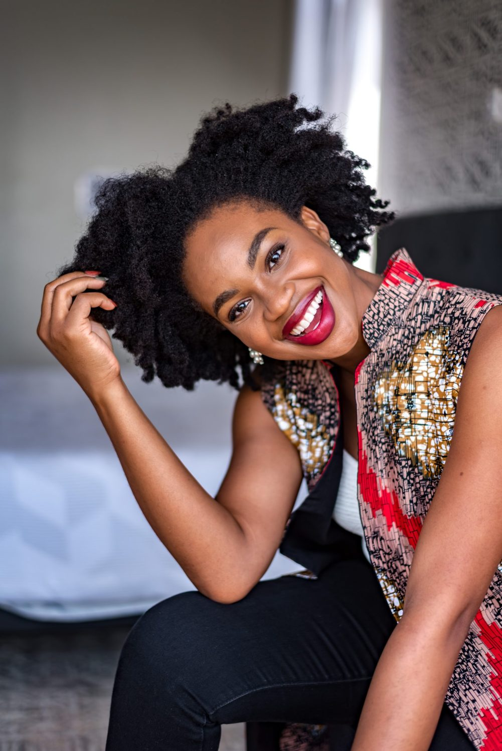 Ijeoma Kola smiling with red lipstick and touching her afro