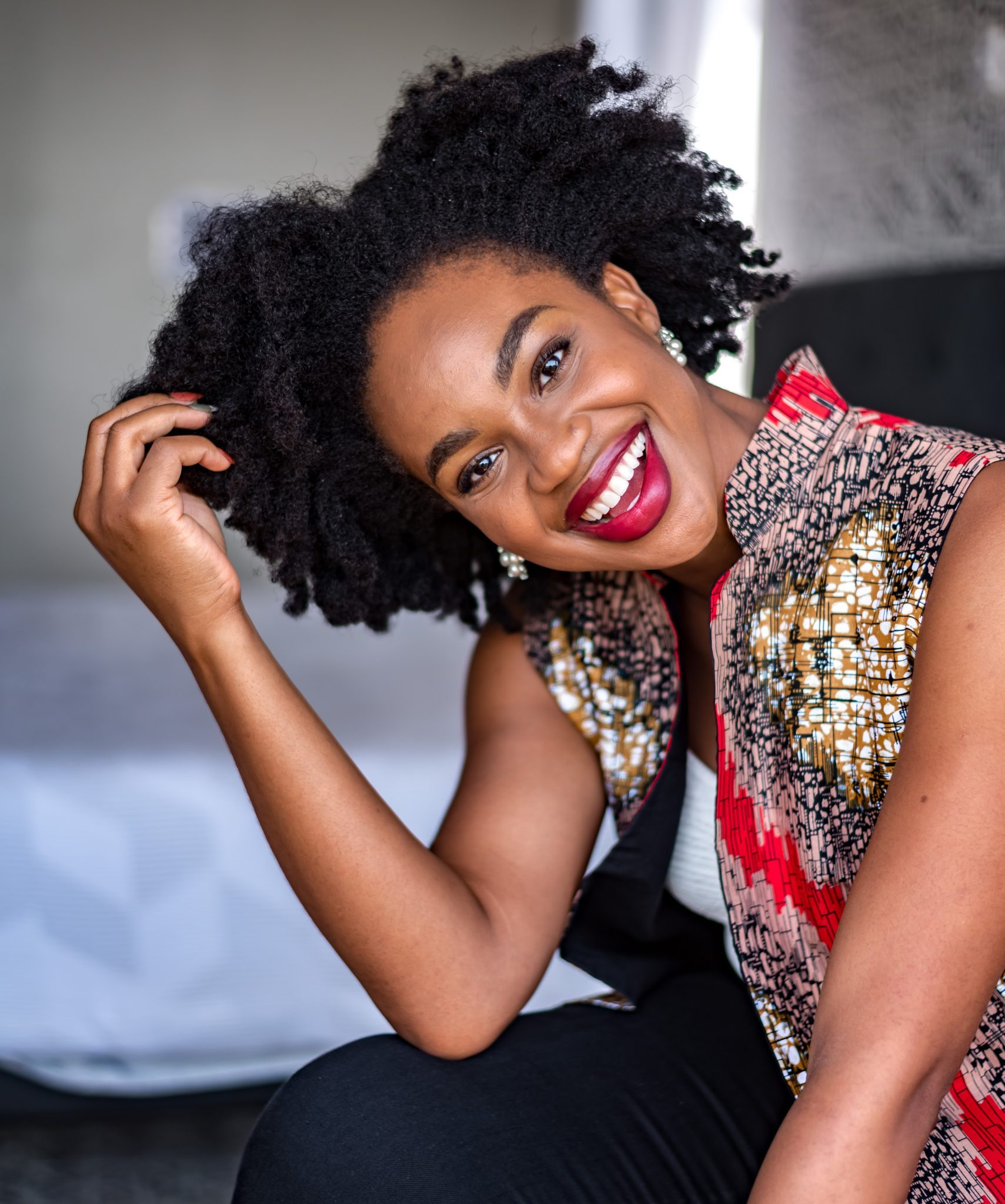 IJeoma.  kola.smiling with red lipstick and touching her afro