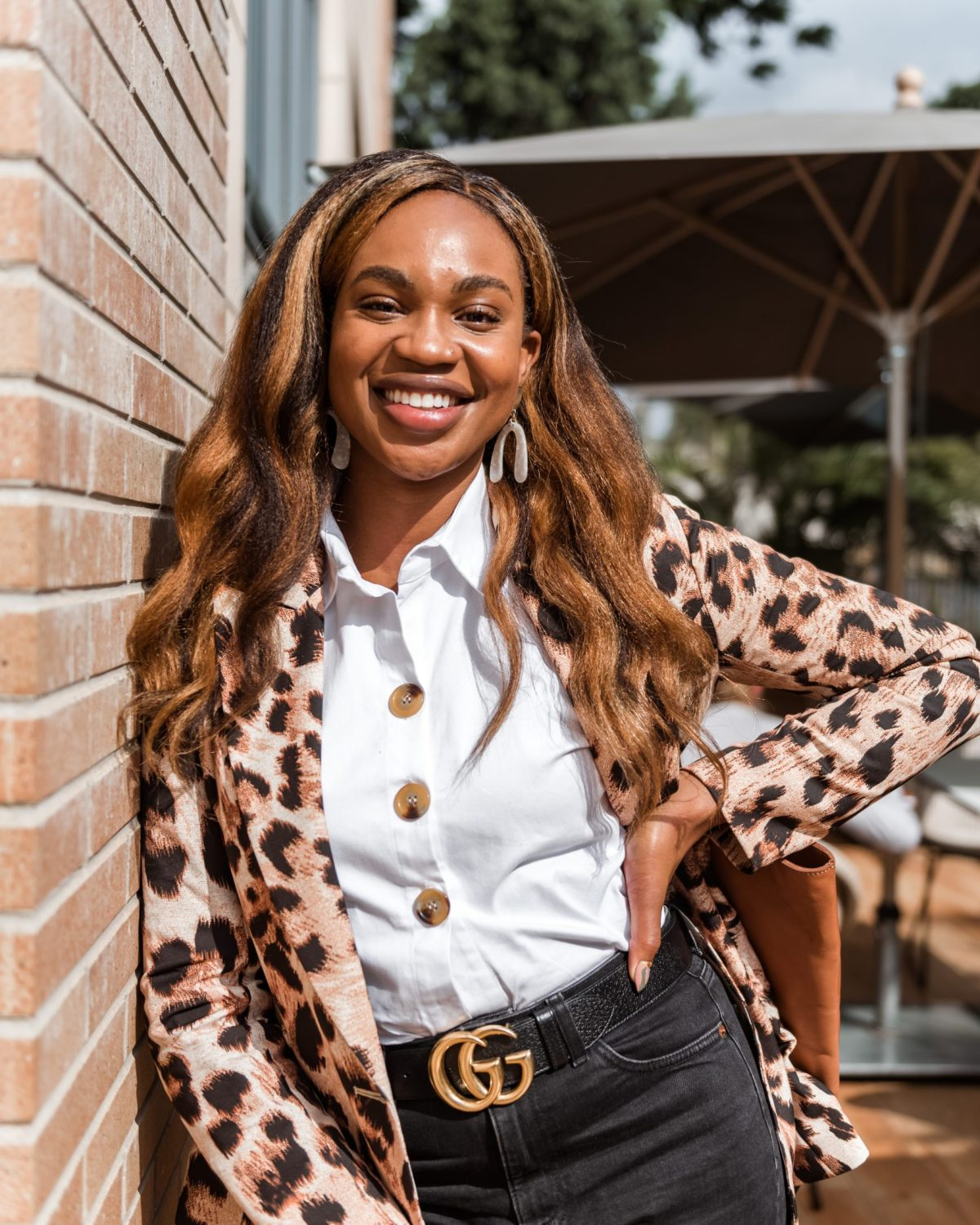 Ijeoma Kola posing with hand on hip in leopard print blazer, white button up shirt and black Gucci belt