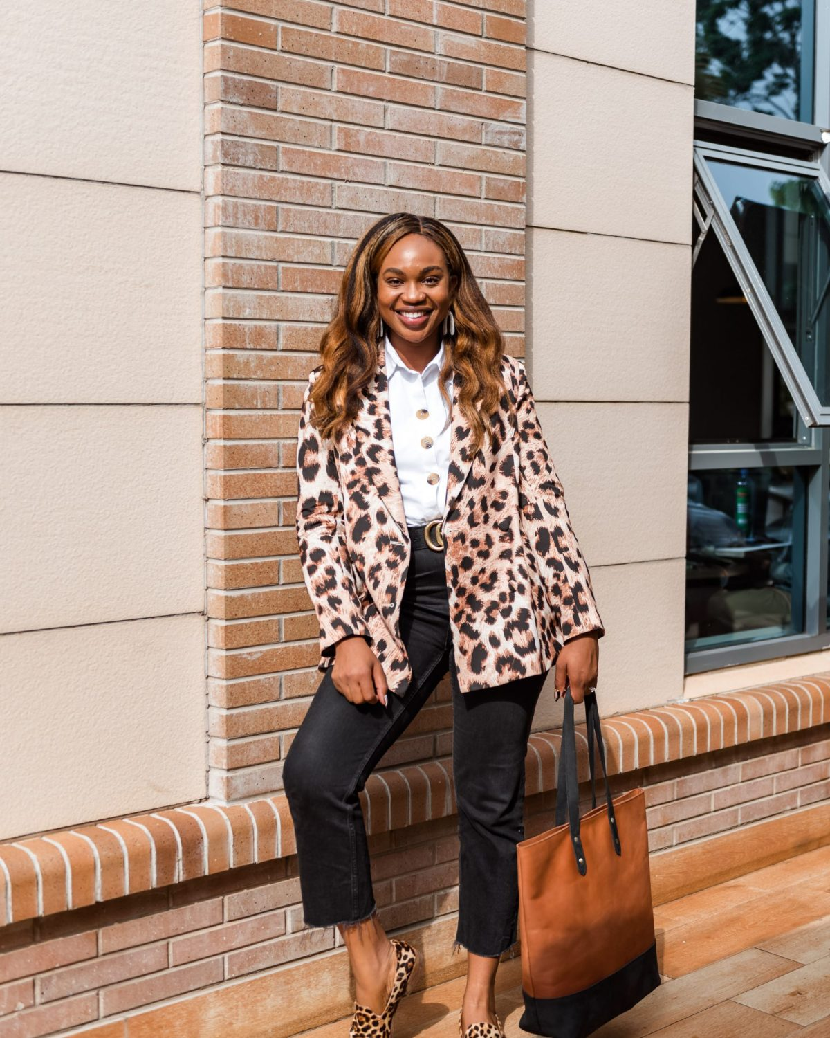 Full outfit shot of Ijeoma Kola posing outside wearing animal print blazer, white shirt, black pants and animal print shoes - How Black Owned Businesses Can Optimize Black History Month
