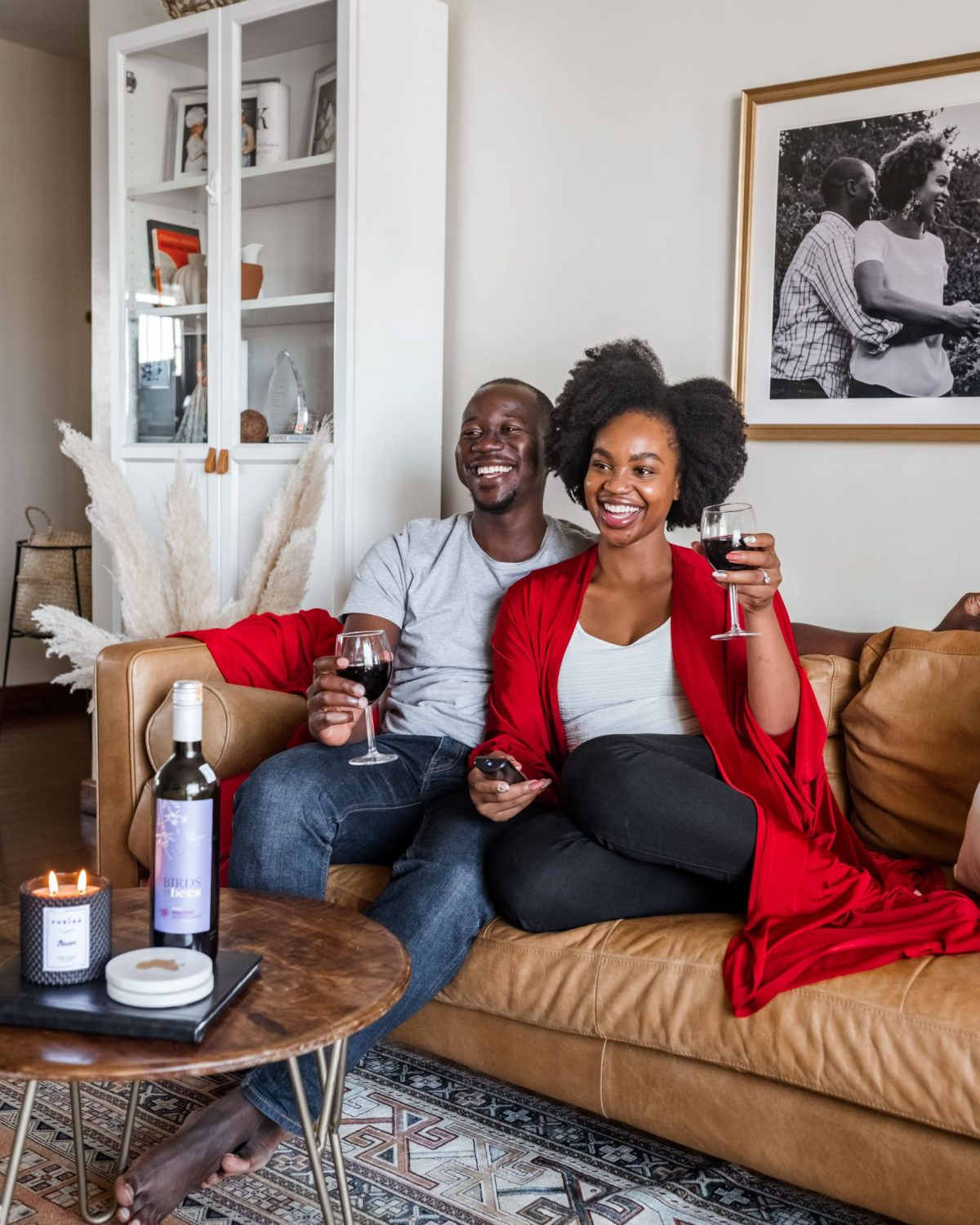 Ijeoma and Jonathan Kola cuddling on couch with wine on Valentine's Day