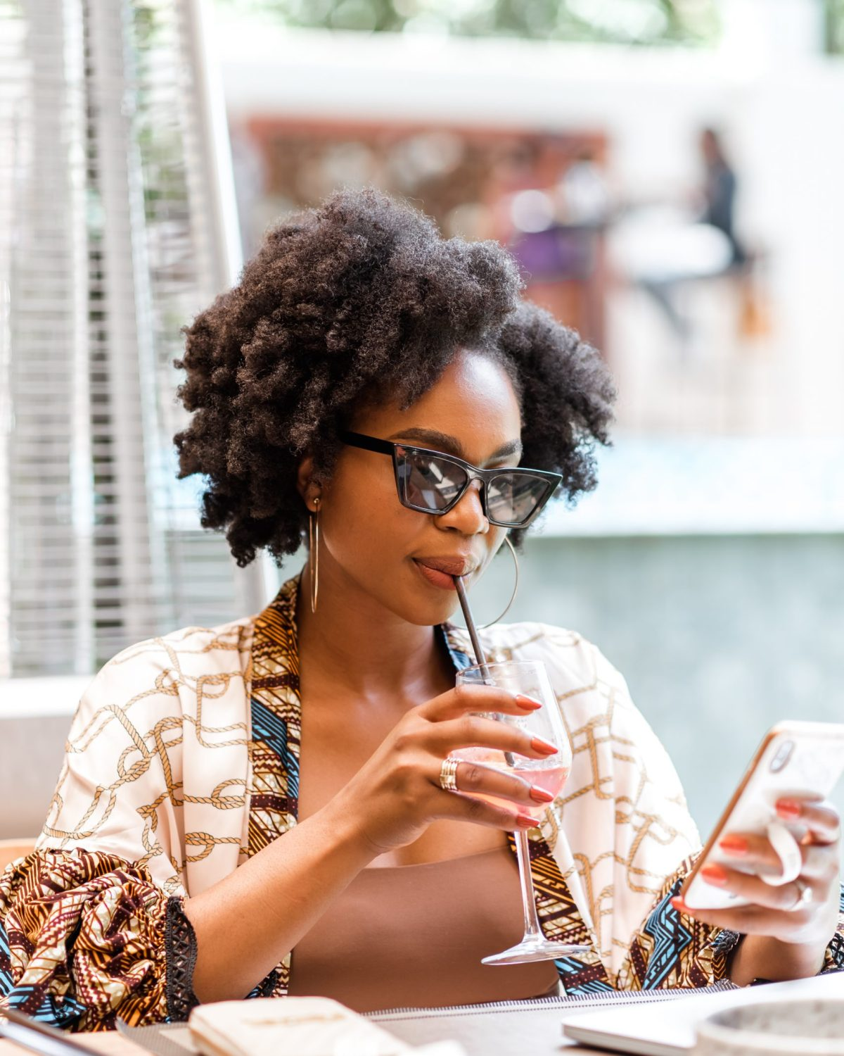 Ijeoma Kola scrolling on phone with sunglasses on and cocktail in hand
