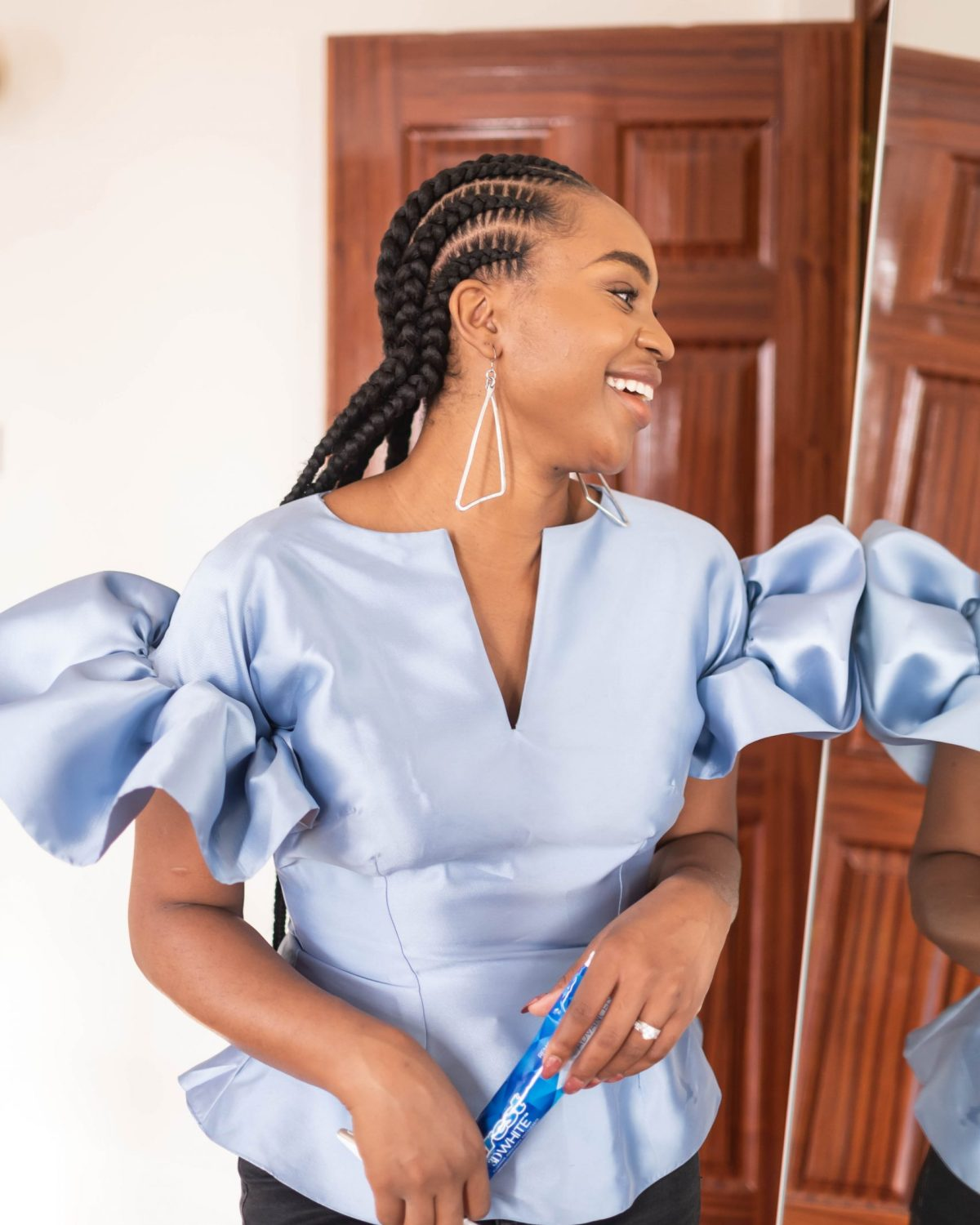 Ijeoma Kola smiling into mirror with Crest toothpaste in hand