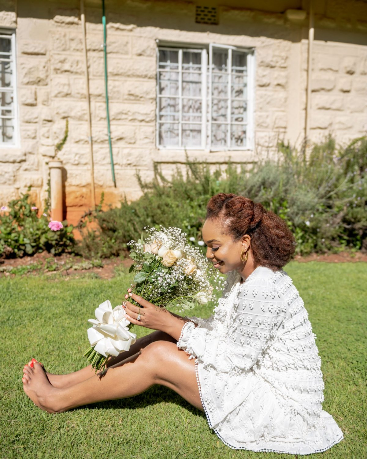 Ijeoma Kola sitting on grass in a white dress in front of a house - Marriage or Mortgage