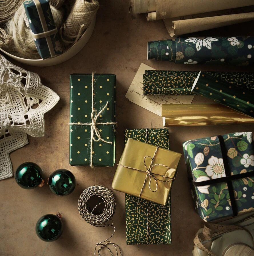 A selection of green and gold baubles, accessories and presents wrapped in VINTER 2020 paper and string.