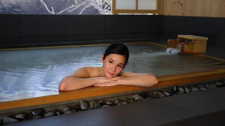 Lady soaking in hinoki onsen bath at Ikeda Spa