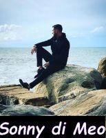 Sonny Meo su una roccia vicino al mare a contemplare il panorama