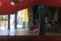 Fedeli buddisti al riparo in un tempio, in attesa che il monsone passi.