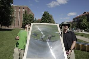 """LENTE FRESNEL PER DISINFETTARE L'ACQUA. Come qualsiasi apparecchio dotato di lampada UV, anche una lente fresnel permette di concentrare i raggi ultravioletti, utilizzando come fonte il Sole. Nell'immagine Paul Shen ed """"Chip"""" Blatchley mentre orientano la lente verso un contenitore d'acqua da disinfettare. (FOTO Prof. Ernest R. Blatchley III)"""