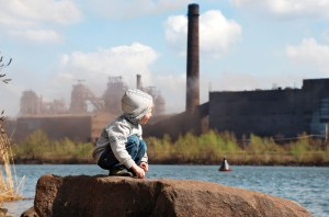 Plaing little boy on the river coast in front of metallurgy plant