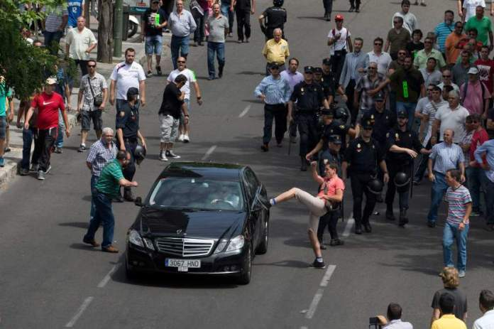A demonstrator kicks a car, suspected to be a private taxi during a 24 hour taxi strike and protest in Madrid, Spain, Wednesday, June 11, 2014. The taxi drivers were protesting against unregulated competition from private companies, in particular, Uber, an international company that puts people in contact with each other to share cars or pay for short journeys in private vehicles within the city. (AP Photo/Paul White)