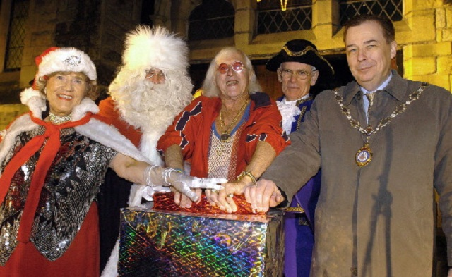 Sir Jimmy Savile switches on the Ilkley Christmas lights in 2006, with help from Shirley Britain, Father Christmas, Ilkley's Town Cryer Chris Richards and Mike Gibbons.