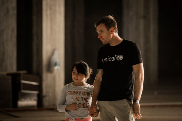 Unicef Ambassador Ewan McGregor walks with Myrna, 10, inside an abandoned mall that her and her family used to live in, Erbil, northern Iraq on July 29, 2016. Unicef Ambassador Ewan McGregor travelled to northern Iraq last week to see how the conflicts sweeping Iraq and Syria are devastating the lives of children, tearing them from their homes and destroying their futures. Tens of thousands of children in Iraq and Syria have been killed, injured, separated from their parents, forced into work, tortured or recruited into fighting. Erbil, northern Iraq, July 29, 2016. © UNICEF/Iraq/Modola16 Unicef UK Ambassador Ewan McGregor in Iraq 2016