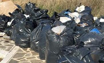 Cataste di cartone e una trentina di sacchi di spazzatura su un marciapiede della circonvallazione