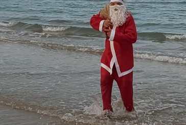 Babbo Natale spunta dal mare con i doni per i bambini