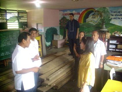 Provincial Environment and Natural Resources Officer Juan delos Reyes (rear left ) and Bangui CENR Officer Alberto Baguio turn-over the 93 pieces of red lauan, tanguili and other hardwood lumber to Bangui Central Elem School Principal Rosabella Nacino. Bangui Mayor Salvacion Cimatu (right)  and other school teachers witnessed the turn-over.
