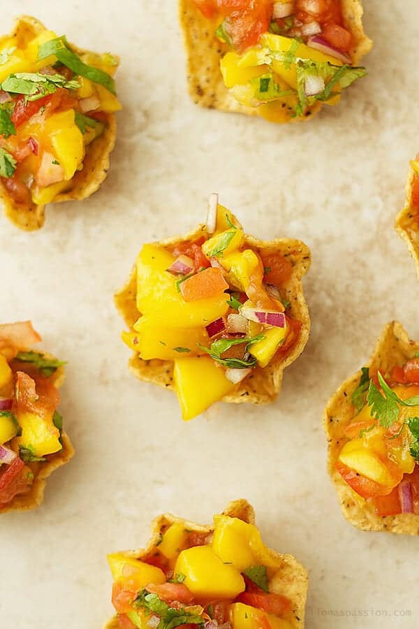 Mango salsa served in mini cups made from corn chips.