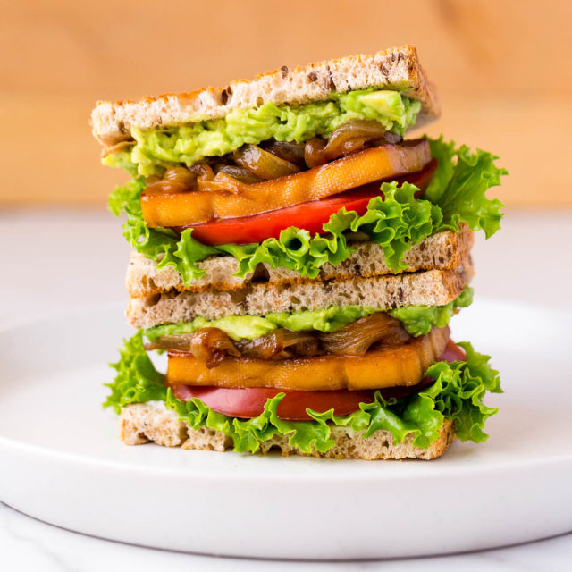 Stacked smoky maple tofu sandwiches on a plate.