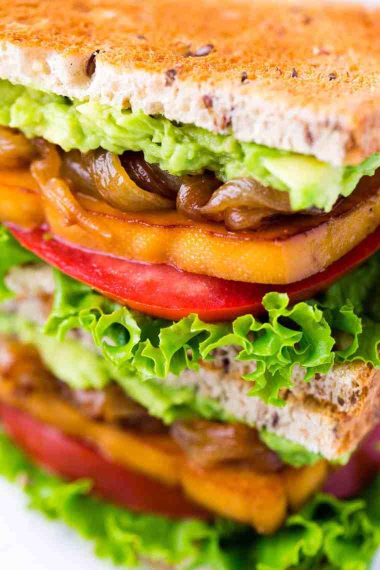 Close up shot of smoky maple tofu sandwich with lettuce, tomatoes, tofu, caramelized onion, and mashed avocado.