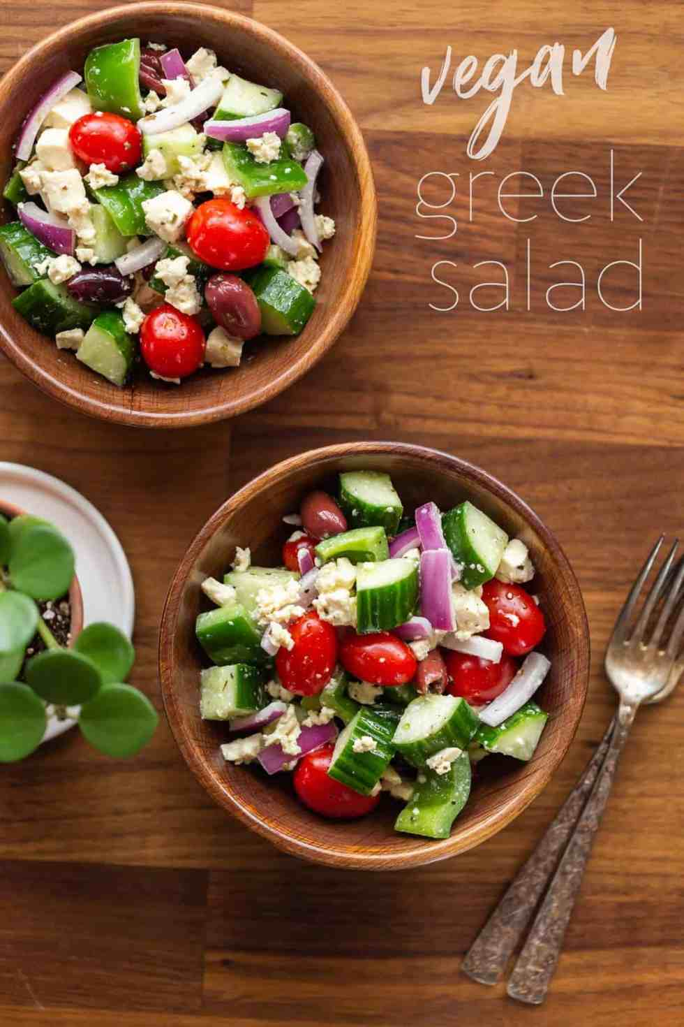 Two individual servings of vegan Greek salad served in small wood bowls on top of a walnut counter top.