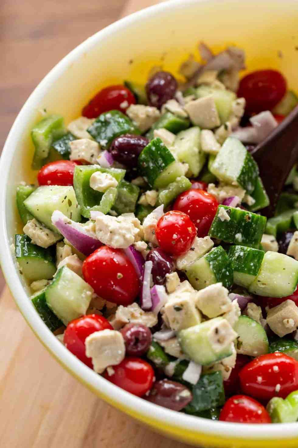 Prepared vegan Greek salad in a large yellow Pyrex serving bowl.