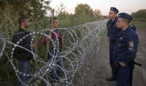 Syrian refugees and Hungarian police chat at the barbed wire fence at the border between Serbia and Hungary, in Roszke, Hungary Friday, Aug. 28, 2015. Hungary deployed police reinforcements to rein in an unrelenting flow of migrants across its porous border Thursday, but refugee activists said the effort appeared futile in a nation whose migrant camps are overloaded and barely delay their journeys west into the heart of the European Union. (ANSA/AP Photo/Darko Bandic)