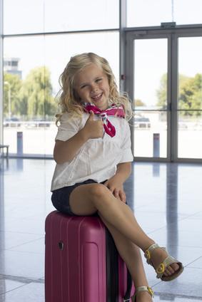 空港でスーツケースにすわる女の子