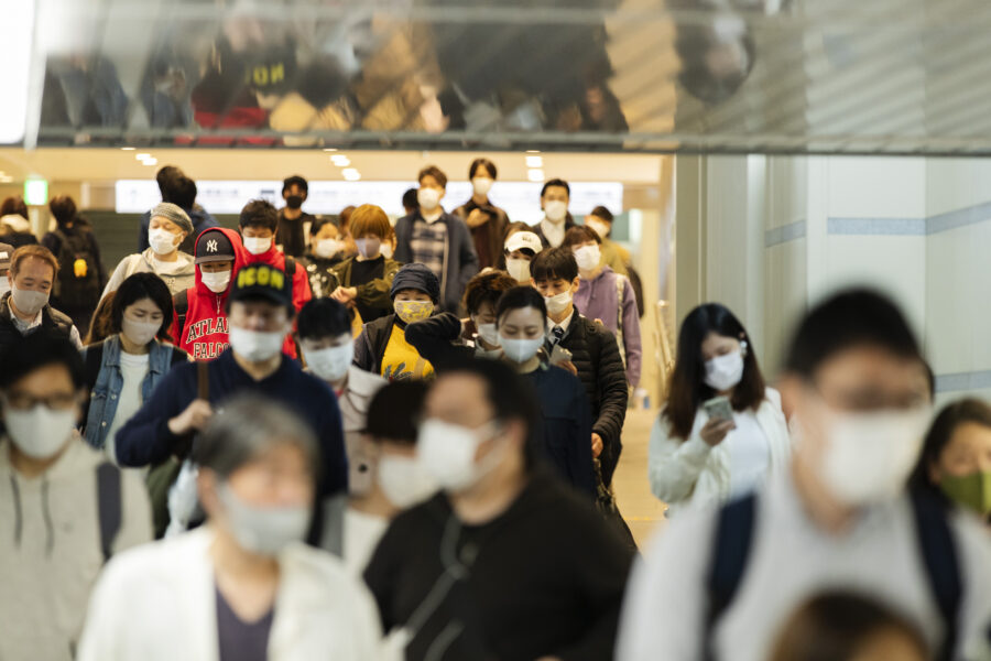People wearing face masks walk between train stations for transit in the famed Namba district of Osaka, western Japan, Saturday, April 17, 2021. (AP Photo/Hiro Komae)