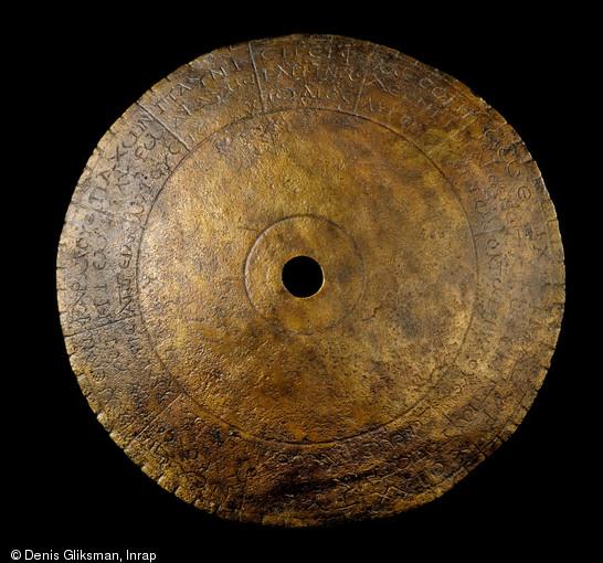 Ledisque astrologique de Chevroches (Nièvre), daté de la fin du IIIe s. de notre ère, 2001.  Constitué d'une tôle en alliage cuivreux de 0,5 mm d'épaisseur percée en son centre, ilprésente un diamètre d'environ 65 mm. Sa courbure permet d'évaluer son diamètre d'origine à 100 mm.