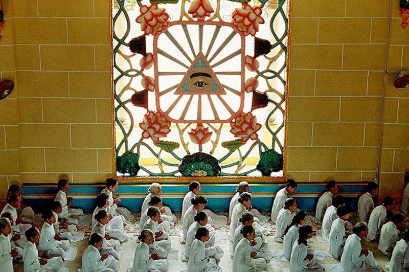 Recueillement sous l'oeil divin, symbole du Caodaïsme, durant la messe de midi. Temple Cao Dai de Tay Ninh, Vietnam, 1997