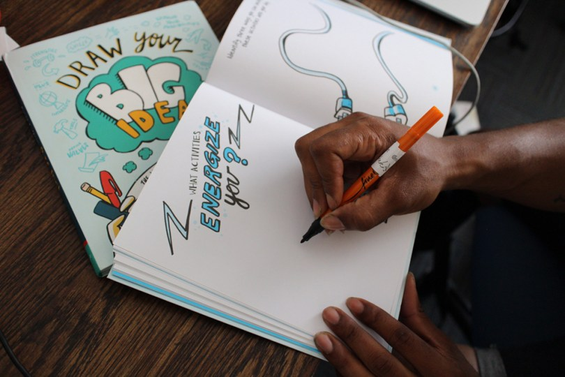 Picture of A Person Writing In A Copy Of Draw Your Big Idea