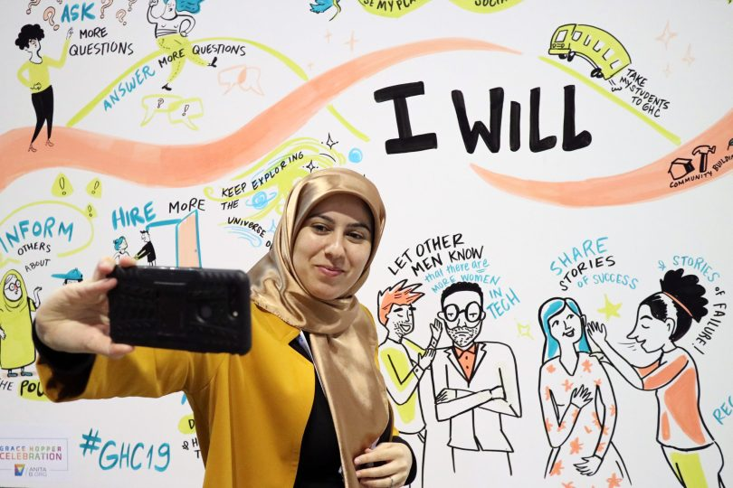 Attendee at the 2019 Grace Hopper Celebration taking a selfie with one of our Social Listening Murals at the Anita B. Booth.