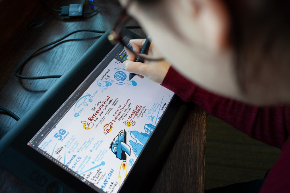 A graphic recorder working digitally in-studio on a clients remote meeting using a Wacom Cintiq drawing tablet.