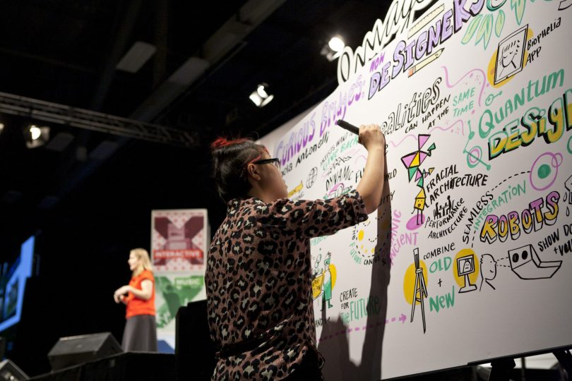ImageThink scribe in the foreground shown graphic recording for a SXSW keynote speaker on stage