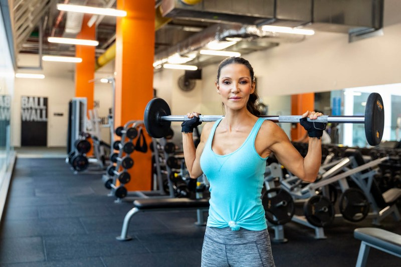 Woman in a gym holding a barbell with weights